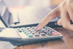 рука женщины рассчитывать калькулятор с предпосылкой нерезкости компьтер-книжки компьютера Стоковое фото RF