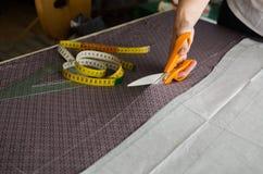Рука женщины режет часть ткани перед шить стоковое изображение rf