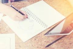 Рука женщины рисуя схему пока она смотрит экран таблетки Стоковое Фото