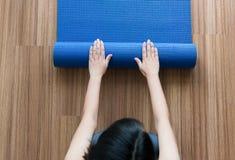 Рука женщины свертывая или складывая голубую циновку йоги после разминки, оборудования тренировки, фитнеса взгляд сверху здоровых стоковая фотография rf