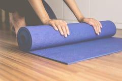 Рука женщины свертывая или складывая голубую циновку йоги после фитнеса разминки, оборудования тренировки здоровых и концепции сп стоковые изображения rf
