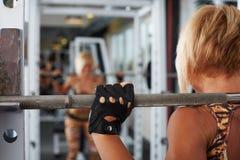Рука женщины спортсмена белокурой делая сидения на корточках Стоковое фото RF