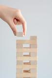 Рука женщины строя башню деревянных блоков на белой предпосылке Стоковое фото RF