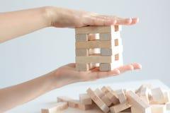 Рука женщины строя башню деревянных блоков на белой предпосылке Стоковая Фотография