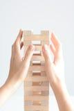 Рука женщины строя башню деревянных блоков на белой предпосылке Стоковое Изображение