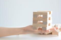 Рука женщины строя башню деревянных блоков на белой предпосылке Стоковые Фотографии RF