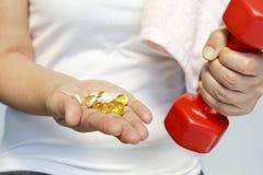 Рука женщины с витаминами и лекарством Стоковая Фотография