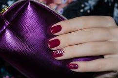 Рука женщины с темнотой - красным дизайном ногтя Стоковое Изображение RF