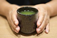 Рука женщины с чашкой зеленого чая Стоковые Изображения RF