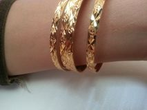 Рука женщины с bangles золота вокруг запястья руки Стоковое фото RF