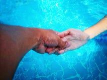 Рука женщины удерживания руки человека стоковая фотография