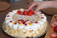 Рука женщины украшает cream торт с клубниками Стоковое Фото