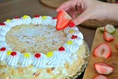 Рука женщины украшает cream торт с клубниками Стоковое фото RF