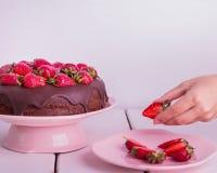 Рука женщины украшенная с шоколадным тортом клубники Стоковые Изображения RF