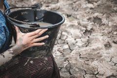 Рука женщины черпает воду на треснутой земле стоковое изображение rf