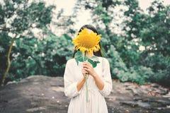 Рука женщин битника держа солнцецвет Стоковое Фото