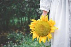 Рука женщин битника держа солнцецвет Стоковые Изображения RF