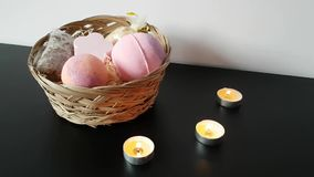 Рука женщин длиной исправляет горящие свечи стоя на таблице рядом с плетеной коробкой с косметиками для купать сток-видео