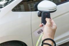 Рука женщин отжимает на аварийной системе автомобиля дистанционного управления Стоковое фото RF