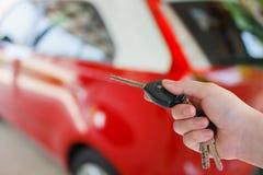 Рука женщин отжимает на сигнале тревоги автомобиля дистанционного управления Стоковое Фото