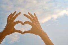 Рука женщин показывая форму сердца стоковая фотография