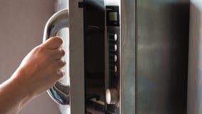 Рука закрывает дверь старой стальной микроволновой печи видеоматериал
