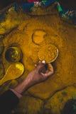 Рука заполняет малую чашку с желтым порошком карри стоковые фотографии rf