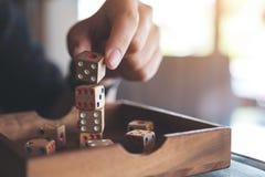 Рука играя и строя деревянная dices Стоковое Фото
