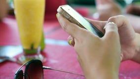 Рука играя умный телефон на тропическом празднике предпосылка smoothies и солнечных очков плодоовощ сток-видео