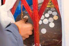 Рука индийского человека кладет монетку на камень для благословлять стоковые фото