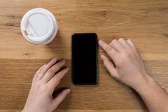 Рука используя взгляд сверху телефона стоковое фото rf