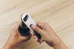 Рука используя консервооткрыватель бутылки нержавеющей стали Стоковые Изображения RF