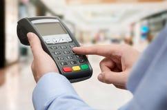 Рука используя машину оплаты кредитной карточки стоковое изображение rf