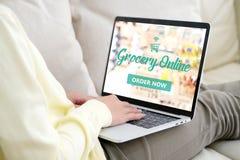 Рука используя портативный компьютер с покупками бакалеи онлайн над голубым стоковое фото