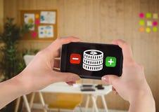 Рука используя телефон с деньгами и плюс и минус кнопки Стоковые Фото