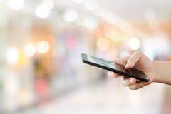 Рука используя умный телефон над предпосылкой света bokeh нерезкости, насмешливой вверх, делом и технологией, интернетом концепци стоковые фото