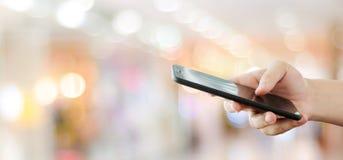 Рука используя умный телефон над предпосылкой света bokeh нерезкости, делом и технологией, интернетом концепции вещей стоковая фотография