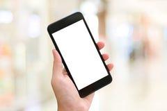 Рука используя умный телефон с пустым экраном над предпосылкой света bokeh нерезкости, делом и технологией, интернетом концепции  стоковые изображения