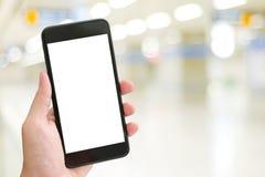 Рука используя умный телефон с пустым экраном над светом b bokeh нерезкости стоковая фотография