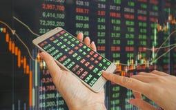 Рука используя мобильный телефон с предпосылкой курса акций стоковое изображение rf