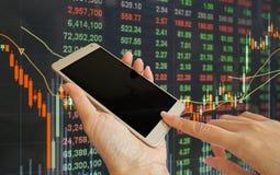 Рука используя мобильный телефон с предпосылкой курса акций стоковые изображения