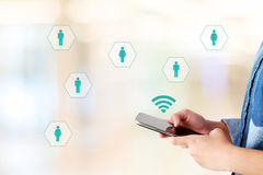 Рука используя умн-телефон с значками сети на предпосылке нерезкости, бесплатная иллюстрация