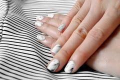 Рука и маникюр, ноготь маникюра Закройте вверх по ногтям гранита серым с черно-белой предпосылкой ткани Стоковое Изображение RF