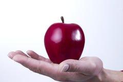 Рука и рука держа яблоко Стоковое Изображение