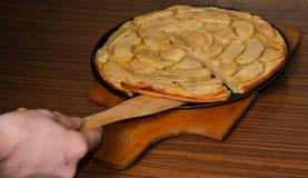 Рука и яблочный пирог, помадка яблочного пирога испекли еду десерта с циннамоном и яблоками на деревянной текстурированной предпо Стоковое Изображение RF