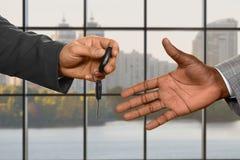 Рука кавказского бизнесмена давая ключ Стоковые Изображения