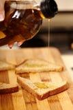Рука кашевара держа бутылку оливкового масла и лить ее над sl Стоковое Изображение