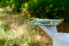 Рука кельнера в белой перчатке держит поднос металла на открытом воздухе стоковые фото