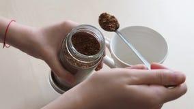 Рука кладет 2 ложки растворимого кофе от стеклянного опарника в кружку акции видеоматериалы