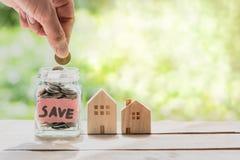 Рука кладя монетку в стеклянный опарник для сохраняя денег для покупая дома Стоковые Фотографии RF